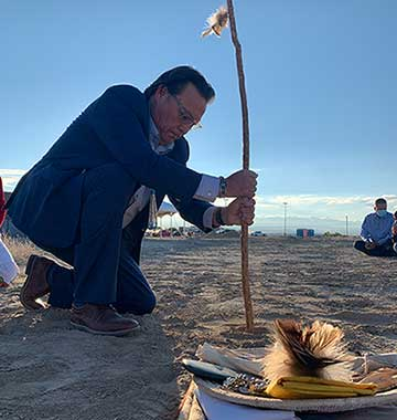 """Diné College President Charles """"Monty"""" Roessel, Ed.D, holds the Planting Stick. The Planting Stick is believed to be the original stick used when the Tsaile (AZ) main campus was built in 1971."""